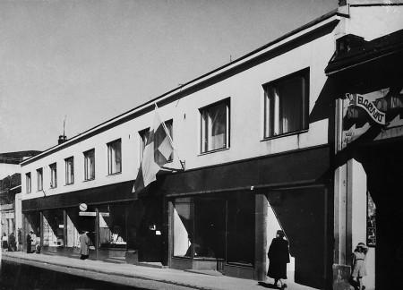 Vuonna 1940 valmistunut kaksikerroksinen liike-ja asuintalo sai vuonna 1954 kaksi lisäkerrosta. Kuva noin vuodelta 1950. Karjalan Puku Oy:n arkisto.