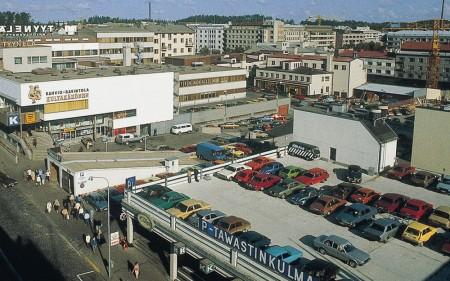 Raatikellarin yläpuolella oli Asemakadun puolella liikesiipi, jonka katolla oli aikaa kuvaavasti autojen parkkipaikka. Kuva vuodelta 1988, Jussi Jäppinen.