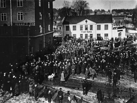 Alkoholiliikkeen aukeamista odotetaan tiilitalon päädyssä huhtikuussa 1932. Kuva Keski-Suomen museo.
